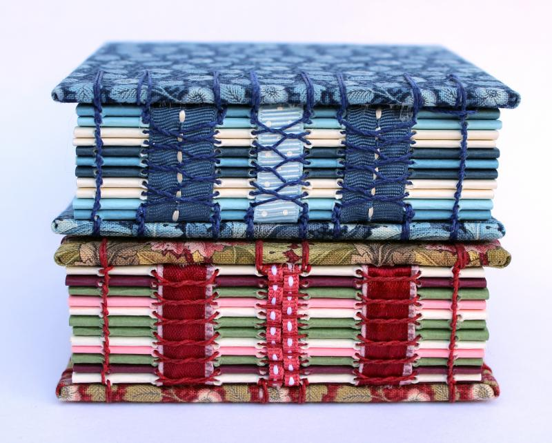 two books bound with open spines in fabric